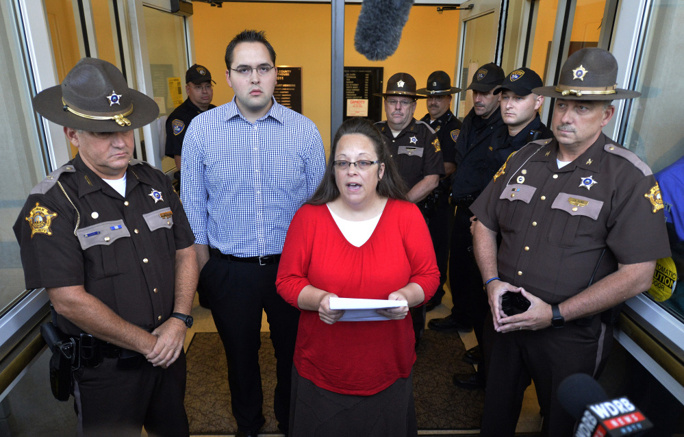 Surrounded by Rowan County Sheriff's deputies, Rowan County Clerk Kim Davis, center, with her son Nathan Davis standing by her side, makes a statement to the media at the front door of the Rowan County Judicial Center in Morehead, Ky., Monday.