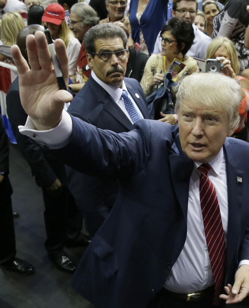 Republican Donald Trump waves to supporters after he bashed illegal immigrants, the media and Republican operatives at a Dallas rally.