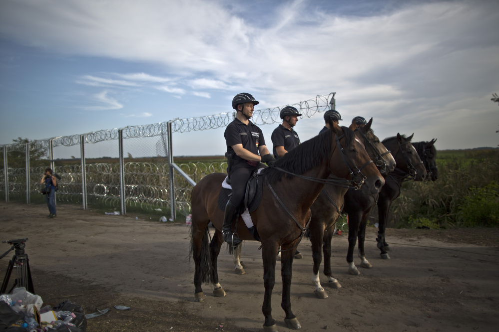 Hungarian police patrol near the fence after the border between Serbia and Hungary was closed, in Roszke, Hungary, on Monday.