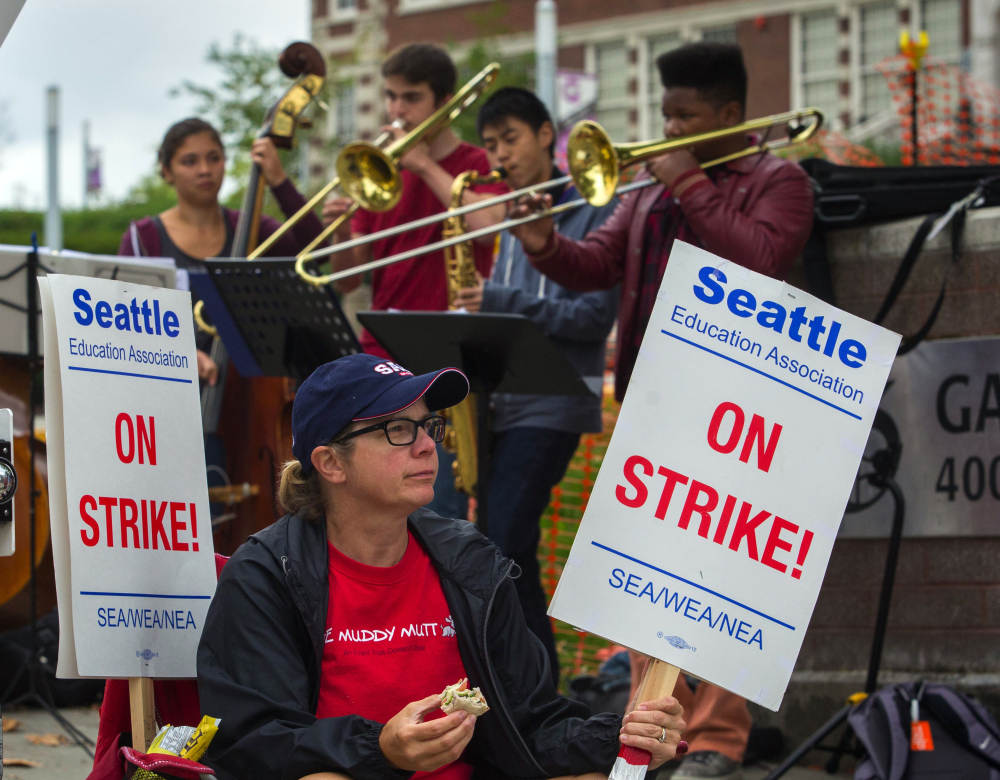Kris McBride, a high school worker, waits to push a traffic-signal button so picketing Seattle teachers can cross the street Monday as student band members play in support.