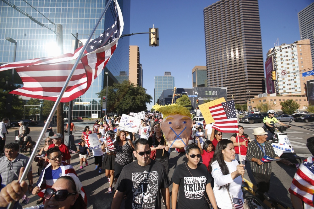 A group marches outside the arena where Republican presidential candidate Donald Trump was holding a campaign event in Dallas on Monday. A conservative group says it will spend up to $1 million on anti-Trump ads.