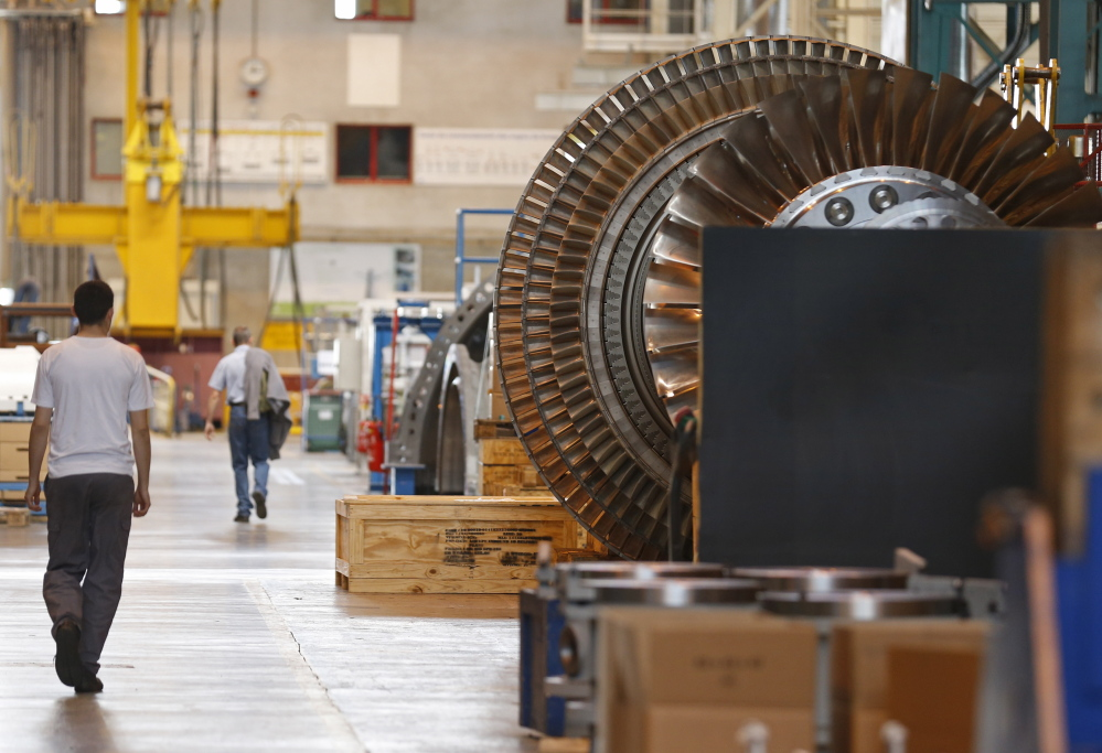 A worker walks past a gas turbine under construction at the gas turbines production unit of the General Electric plant in Belfort, France.