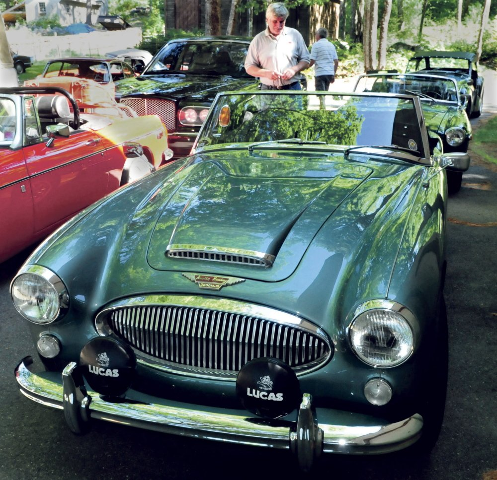 Ray Morrow of Smithfield admires an Austin Healey 3000 on Tuesday at the home of Steve and Janet Towle in North Belgrade. The car was one of a caravan of British-made cars on their way from Nova Scotia to Stowe, Vermont, for the British Invasion car show.