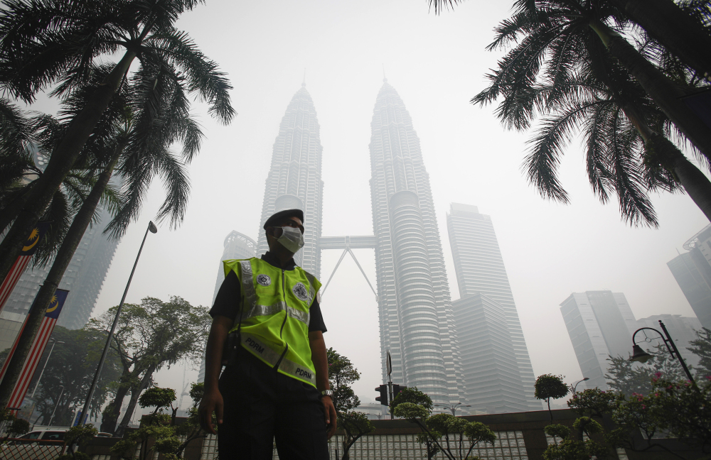 A masked Malaysian police officer stands guard in front of Petronas Twin Towers shrouded by haze in Kuala Lumpur, Malaysia. on Monday.