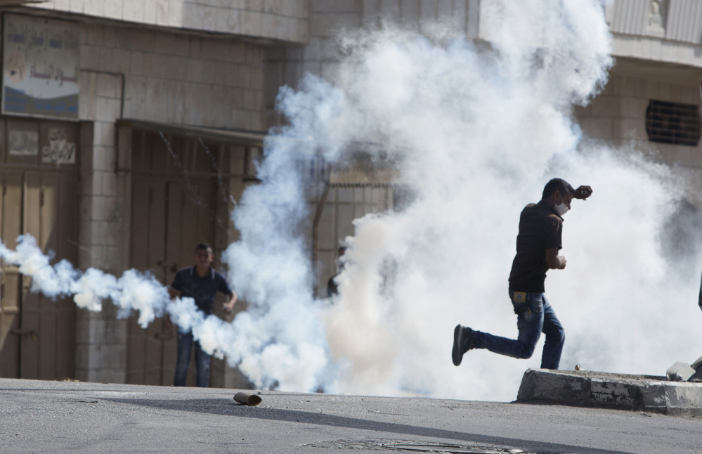 A Palestinian man runs for cover from tear gas fired by Israeli soldiers after a demonstration Tuesday in solidarity with Jerusalem protesters in the West Bank town of al-Ram.