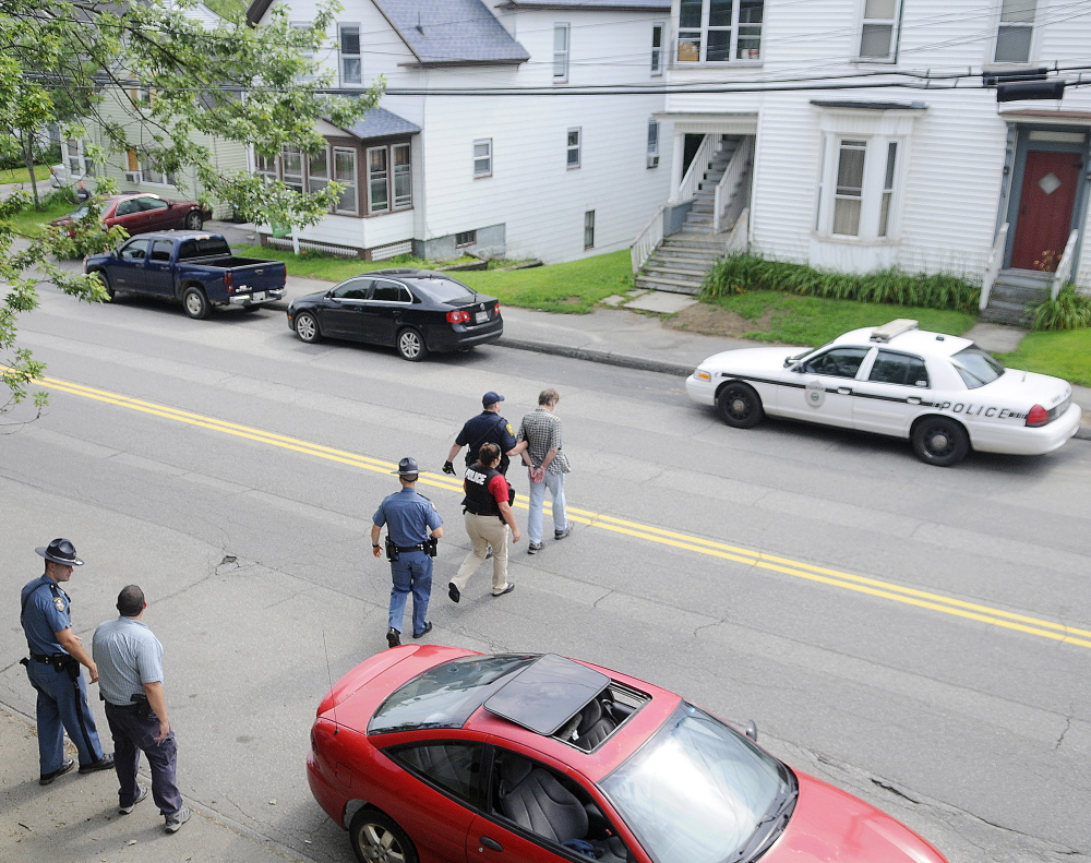 An Augusta police detective, Maine State Police troopers and parole and probation officers escort a man arrested on outstanding warrants to a waiting cruiser on Northern Avenue in Augusta on July 30. State and county law enforcement officers accompanied Augusta police in door-to-door walks through several neighborhoods in Augusta as part of the city Police Department's Operation Hot Spot program.