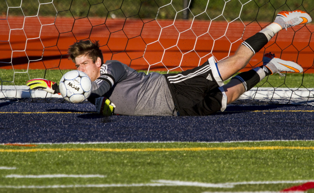 Thornton Academy goalkeeper Andrew Coleman, a senior, dives for one of eight saves Tuesday against Portland at Fitzpatrick Stadium. The teams played to a 0-0 tie.