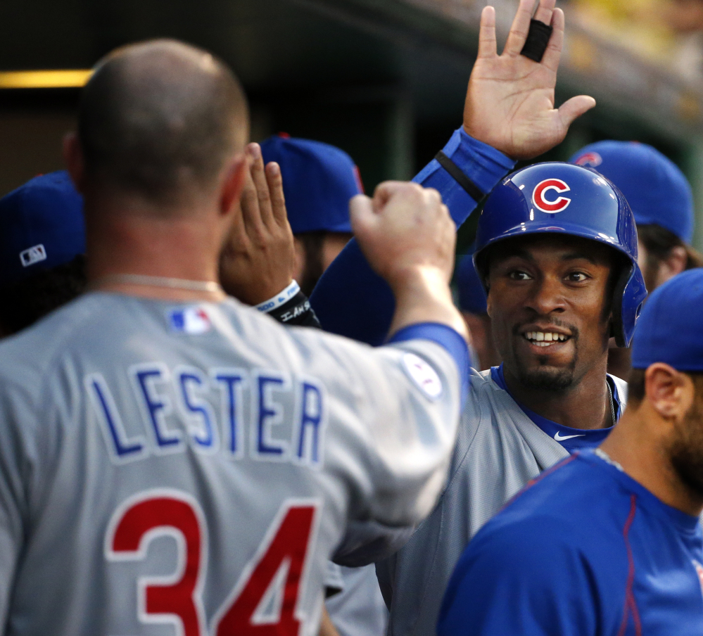 Austin Jackson, second from right, celebrates with Jon Lester in the second game of Tuesday's doubleheader. The Cubs and Pirates split.
