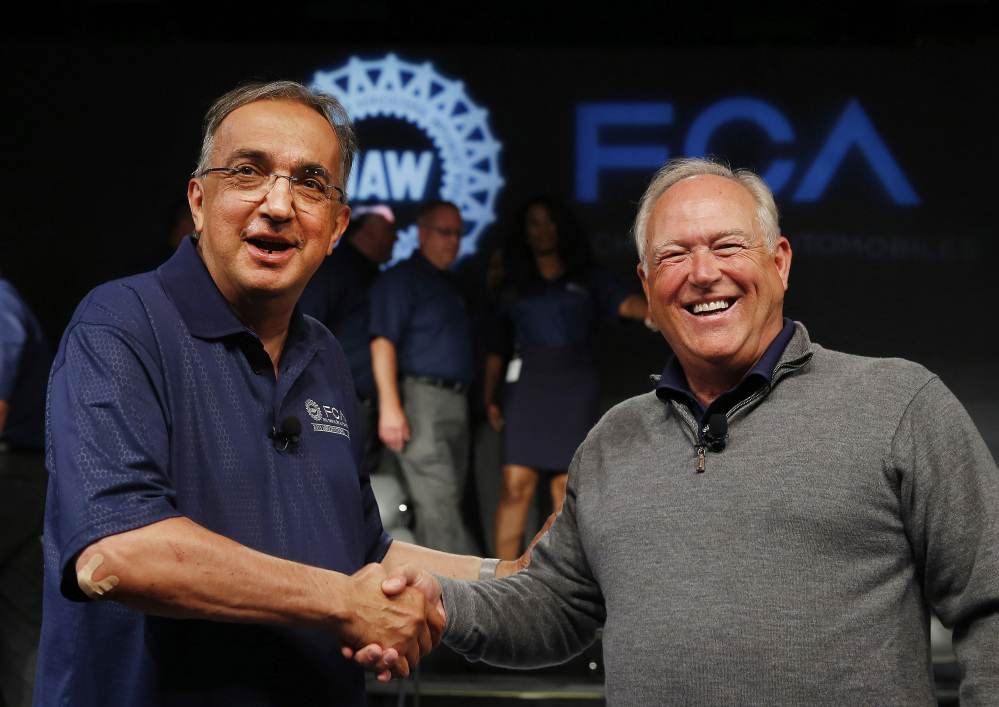 Fiat Chrysler Automobiles CEO Sergio Marchionne, left, and United Auto Workers President Dennis Williams shake hands during a ceremony to mark the opening of contract negotiations in Detroit in July. (AP file photo/Paul Sancya)
