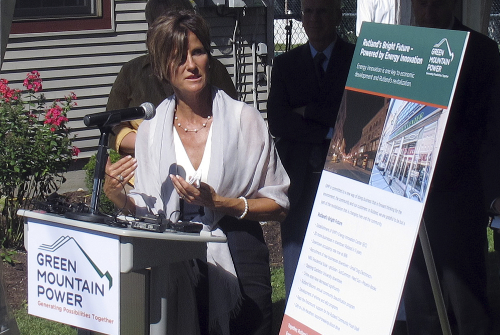 """Green Mountain Power President Mary Powell stands outside the solar-paneled home of Rob and Janet McClallen in Rutland, Vt., on Tuesday. """"Ideally we want to stay ahead and we want to stay ahead through innovation,"""" Powell said."""