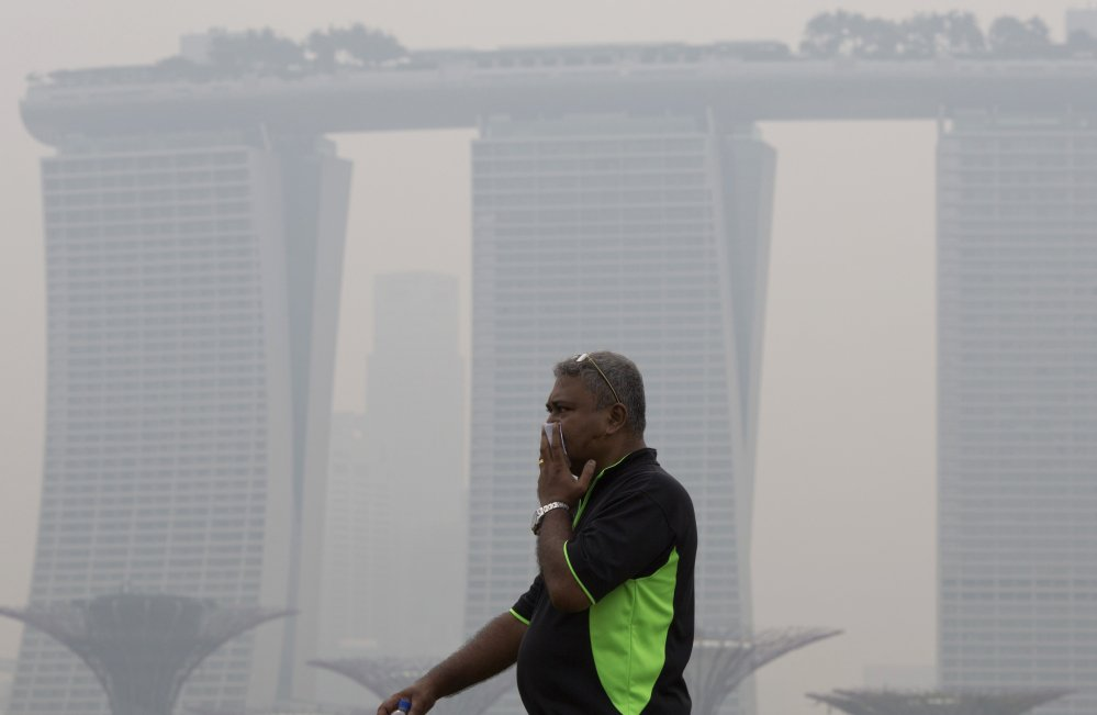 A man covers his nose during a hazy day in Singapore. Air pollution is killing 3.3 million people a year worldwide, says a study that includes this surprise: Farming plays a large role in smog and soot deaths in industrial nations.