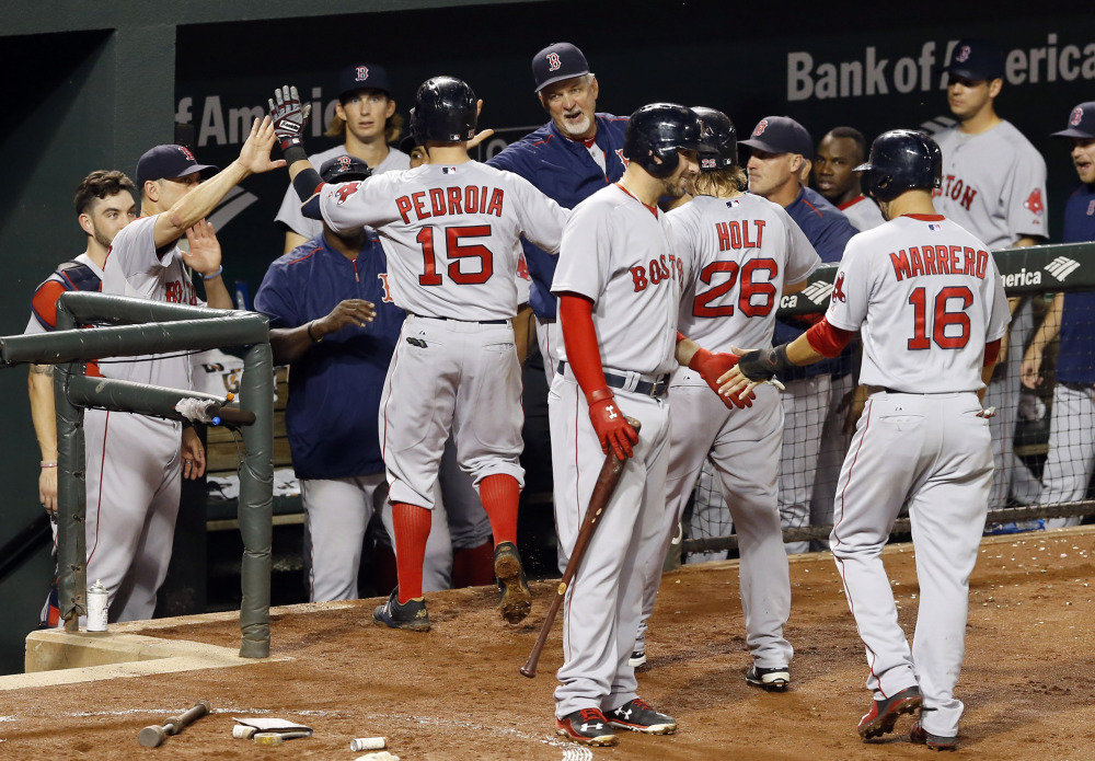 Boston's Dustin Pedroia (15) high-fives teammates in the dugout after driving in Brock Holt (26) and Deven Marrero (16) on a three-run home run in the fourth inning against Baltimore on Wednesday in Baltimore. The Associated Press