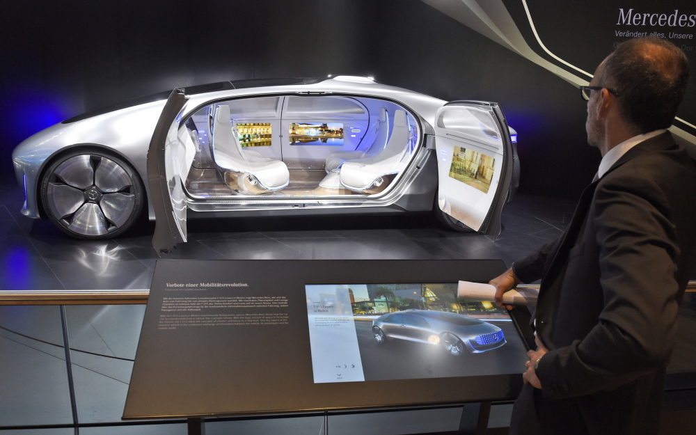 A visitor looks at the 'F 015 Luxury in Motion' autonomous driving vehicle at the Mercedes stand Tuesday, the first press day of the Frankfurt Auto Show IAA in Frankfurt, Germany. The car show runs through Sept. 27.