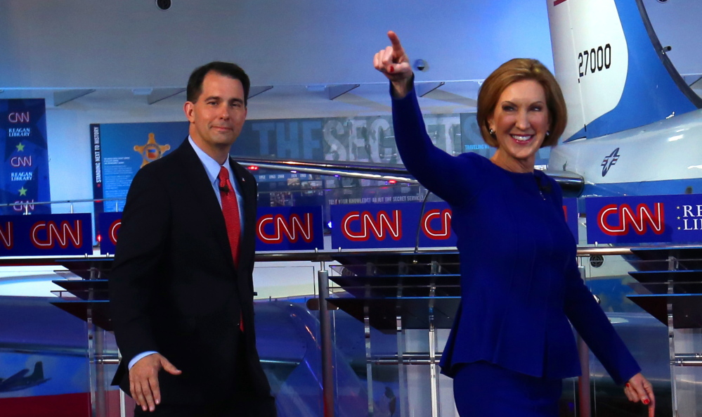 Republican presidential candidates Scott Walker, left, and Carly Fiorina take the stage at the Reagan Library in Simi Valley, Calif., on Wednesday. The debate's tone signaled that the campaign is moving into a more serious phase.