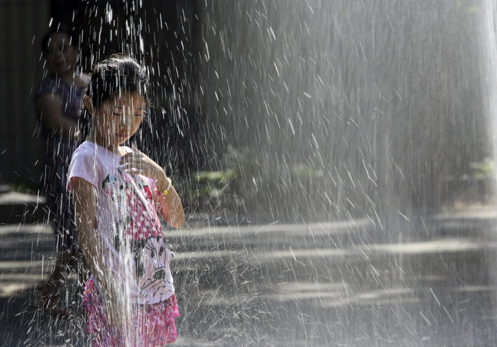 A child plays in the sprinklers of Seward Park in New York in August. The National Oceanic and Atmospheric Administration announced Thursday that last month, this past summer and the first eight months of 2015 all broke global records for heat.