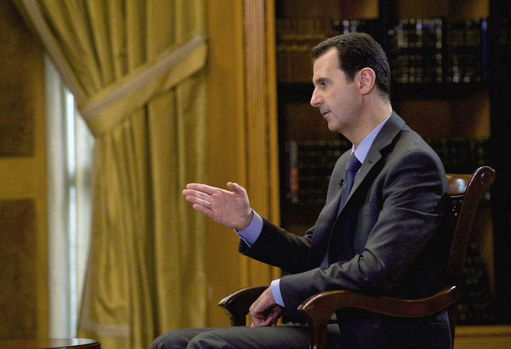 "FILE - In this file photo released Wednesday, March 4, 2015, by the Syrian official news agency SANA, Syrian President Bashar Assad speaks during an interview with Portuguese state television, RTP, in Damascus, Syria. Speaking in an interview with Russian media, Tuesday, Sept. 15, 2015, Assad said the refugee crisis now hitting Europe is a direct result of the West's support of ""terrorists"" in Syria. The Russian president has said it is impossible to defeat the Islamic State group without cooperating with Damascus, and in recent days has sent about a half-dozen battle tanks and other weaponry to Syria. (AP Photo/SANA, File)"
