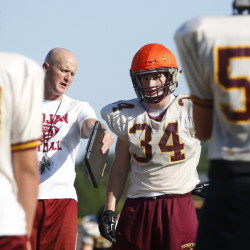 Owen Elliott, a linebacker and senior co-captain for Thornton Academy, receives instruction from Coach Kevin Kezal. The coach of the defending state champions tries to make sure nonstarters get plenty of chances as underclassmen, a strategy that continues to pay off.