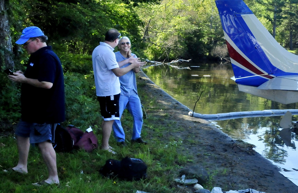 Staff photo by David Leaming Sandy Turbyne, right, speaks with plane passenger Rick Stoppe beside a plane that was forced to land because the engine's oil pressure dropped Thursday on Wesserunsett Lake in East Madison. Turbyne assisted by towing the plane to shore. At left is passenger Perry Bryant.