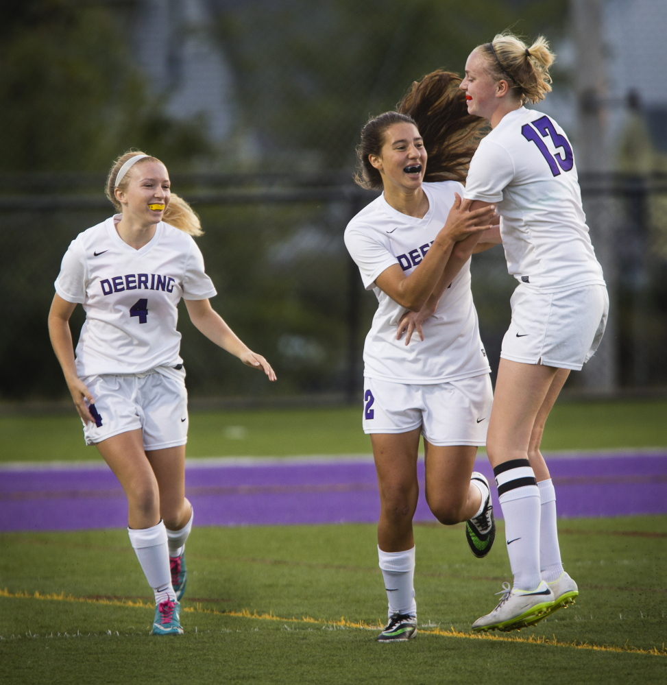 Meghana Clere, center, celebrates with teammate Cora Melcher after scoring a first-half goal against Sanford. Joining in for the Rams is Luci Santerre. Deering built a 2-0 halftime lead before Sanford rallied.