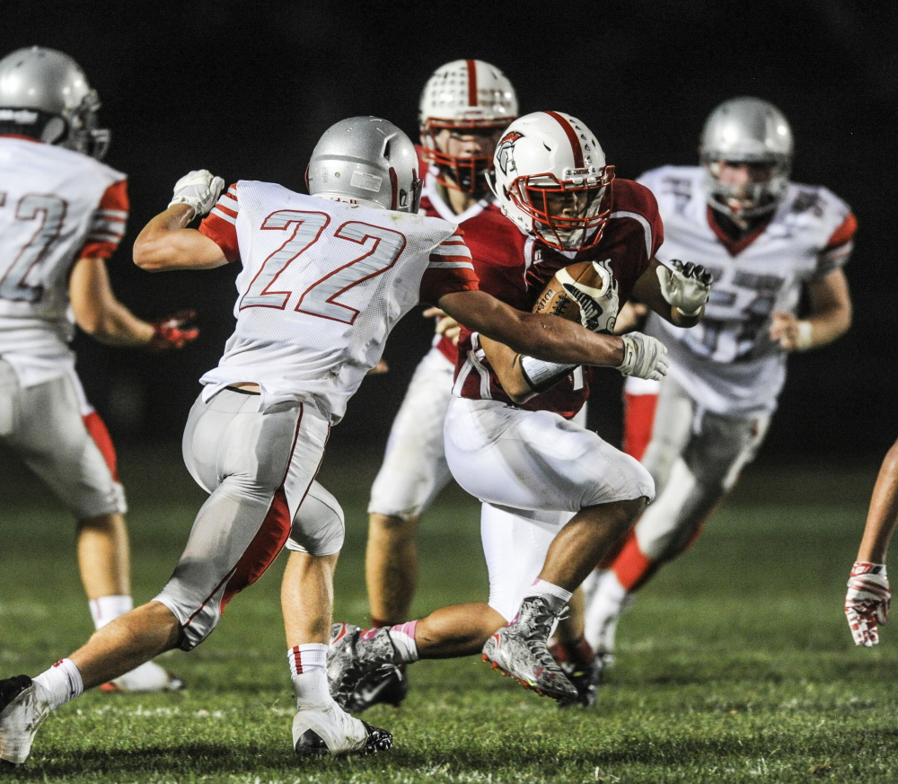 SANFORD, ME - SEPTEMBER 18: Sanford running back Zach Kang attempts to make it past the line of scrimmage while South Portland defensive back Spencer Houlette goes to tackle at Sanford High School in Sanford, ME on Friday, September 18, 2015. (Photo by Whitney Hayward/Staff Photographer)