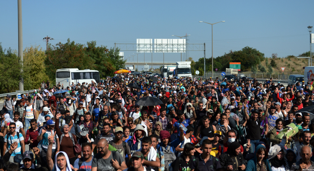 Hundreds of migrants march down a highway toward Turkey's western border with Greece and Bulgaria, near Edirne, Turkey, on Friday.