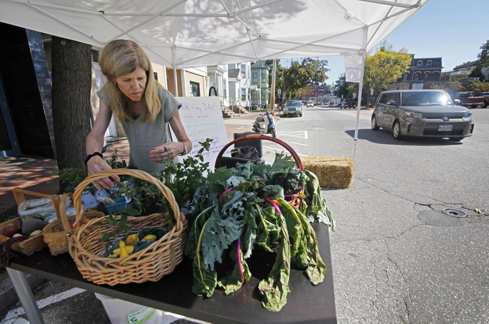 "Anne Spelman tends to fresh vegetables in a parking spot along Congress Street on Friday. Passers-by were welcome to take vegetables in return for ""love"" for Bramhall Square – a small, public space at the intersection of Deering Avenue and Congress and Bramhall streets. Jill Brady/Staff Photographer"