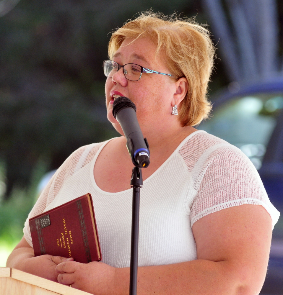 Simonne Maline, executive director of the Consumer Council System of Maine, holds a copy of a 1901 Maine Insane Hospital report as she speaks during a dedication of a marker Friday in memory of people who died at the former Augusta Mental Health Institute at Cony Cemetery in Augusta.
