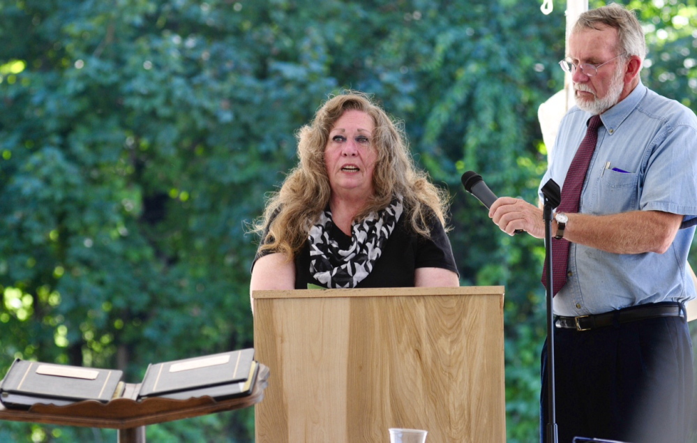 Karen Evans speaks as Peter Driscoll holds the microphone during Friday's dedication of a new monument to honor those who died while at the Augusta Mental Health Institute.