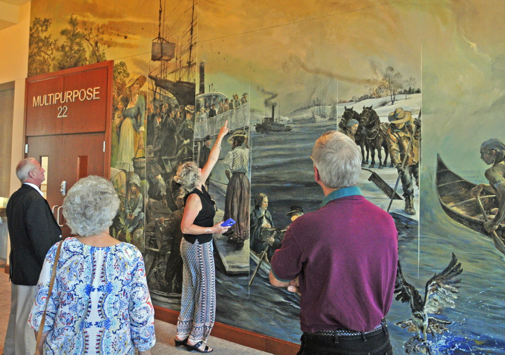 Lisa Gilbert points out an image of Maine Supreme Judicial Court Chief Justice Leigh Saufley standing at a ship railing in the large mural painted by Christopher Cart before the ceremonial opening Friday at the new Capital Judicial Center in Augusta. Cart, of Hallowell, said all the faces are based on real people, including some who helped build or now work in the building.