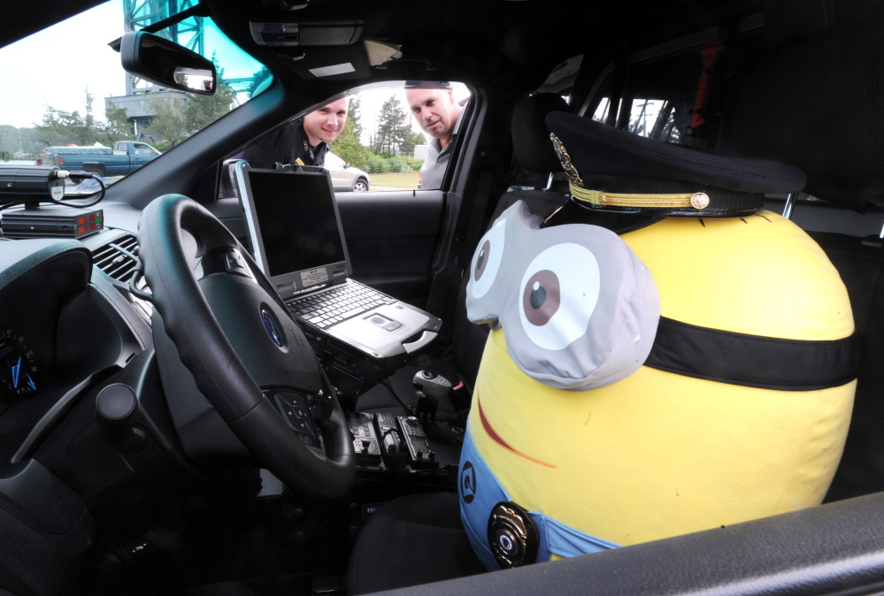 Bourne Lt. Brandon Esip, left, and Detective Sgt. John Stowe look at the Minion doll they use on Facebook to pass along department information. It's this kind of goofy, imaginative content that has made the police department's Facebook page popular.