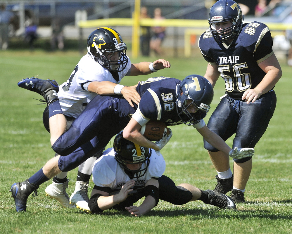 Evan Porter of Traip Academy is tackled by Maranacook's Drew Davis, bottom, and Zach Lacasse. Davis and Lacasse also scored fourth-quarter touchdowns to break a scoreless tie.