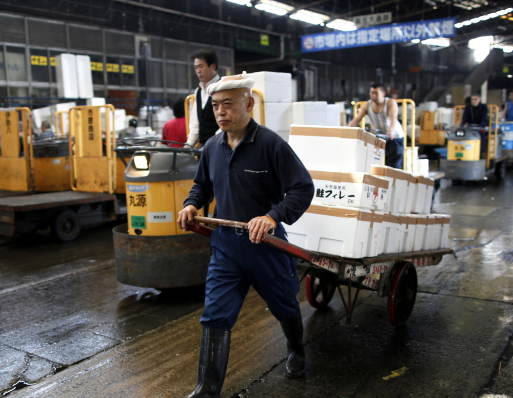 A fish dealer pulls a cart carrying marine products in containers made of styrofoam after the day's auction at Tsukiji Wholesale Market in Tokyo.