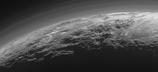 New Horizons photo released Thursday by NASA shows the atmosphere and surface features of Pluto backlit by the sun.