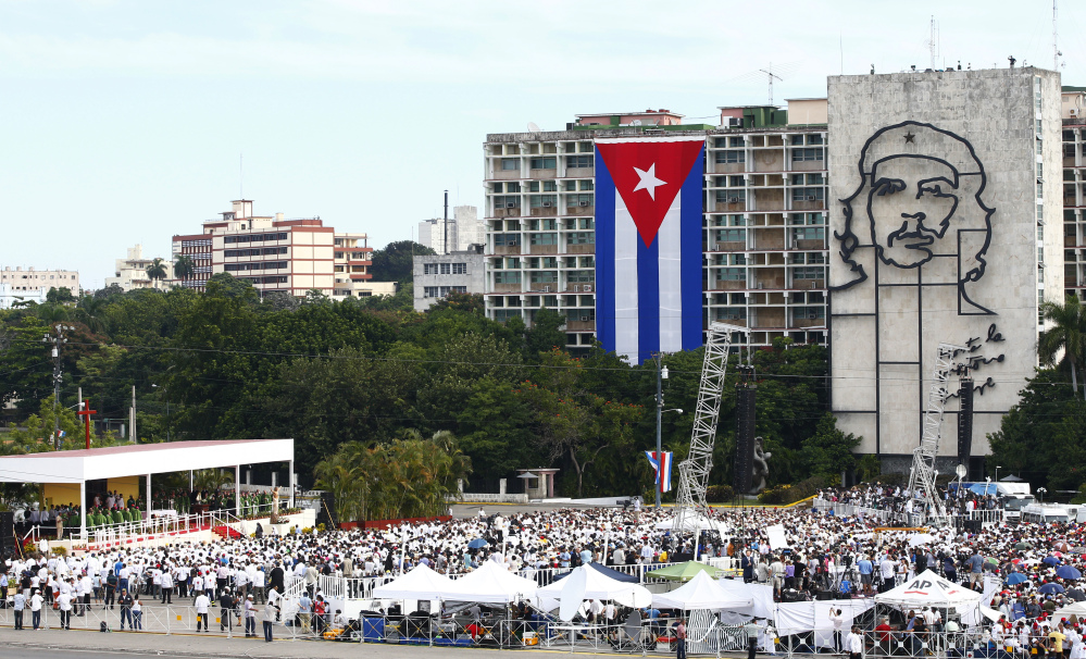 "People gather in Revolution Square as Pope Francis celebrates Mass in Havana, Cuba, on Sunday, where a sculpture of revolutionary hero Ernesto ""Che"" Guevara and a Cuban flag decorate government buildings."