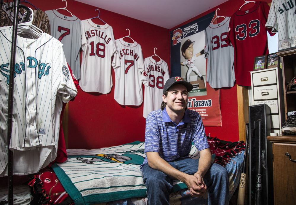 "Joey Morrill, a senior chemistry major at the University of Southern Maine, sits amid the Sea Dogs memorabilia displayed in the room of his brother, Dom, 15. Collecting game-worn jerseys is ""almost like a hunt to see which one you can get next,"" Morrill said."
