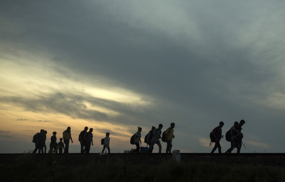 Migrants walk along the railway tracks near the town of Roszke, Hungary. Among the tens of thousands fleeing war and despair in the Middle East are many who have escaped areas ruled by Islamic State extremists who deliver harsh punishments to those who break strict rules.