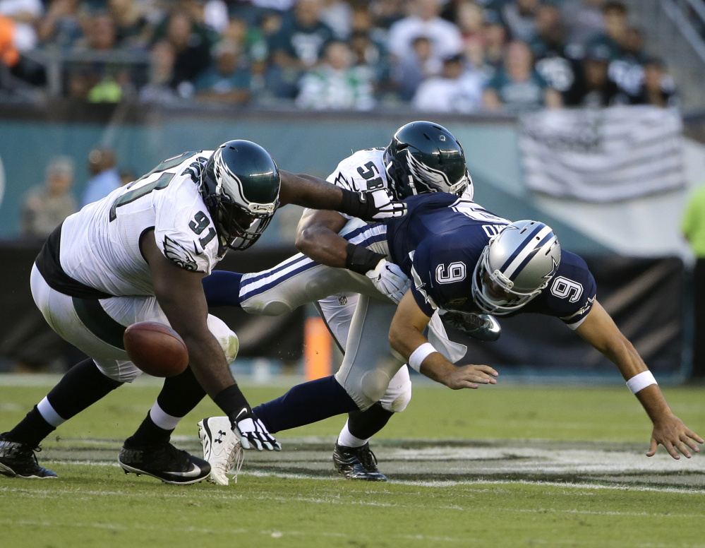 Cowboys quarterback Tony Romo fumbles while being sacked by Jordan Hicks of the Eagles during Dallas' 20-10 win Sunday. Romo suffered a broken collarbone.