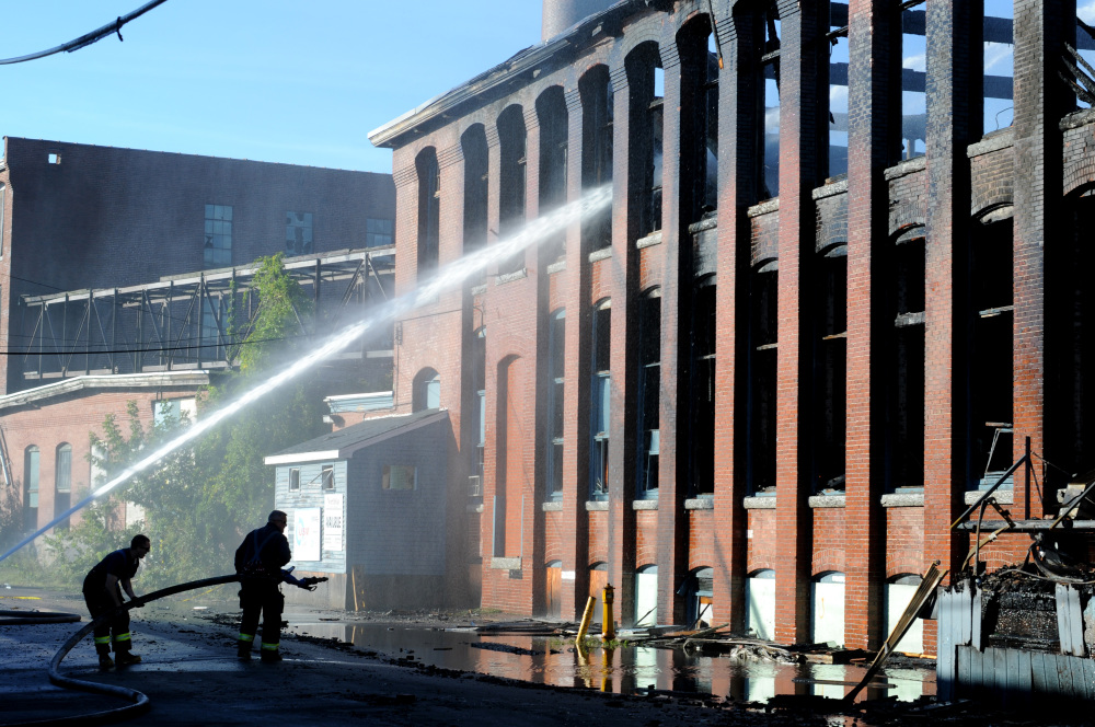 Firefighters were still hosing down hot spots and pumping water onto the former Hudson Manufacturing building in Haverhill, Mass., on Monday. The building caught fire around 5 p.m. Sunday and smoke was visible 20 miles away.