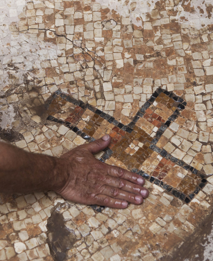 A worker for the Israel Antiquities Authority shows a cross on a mosaic floor at the archaeological site at Ben Shemen Forest.