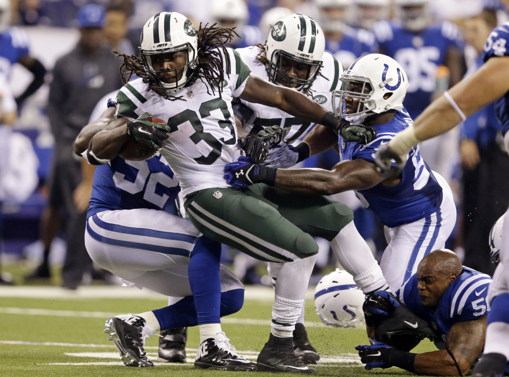 Colts linebacker Jerrell Freeman, bottom right, loses his helmet as he helps tackle Jets running back Chris Ivory, 33, during a 20-7 win by the Jets at Indianapolis on Monday.
