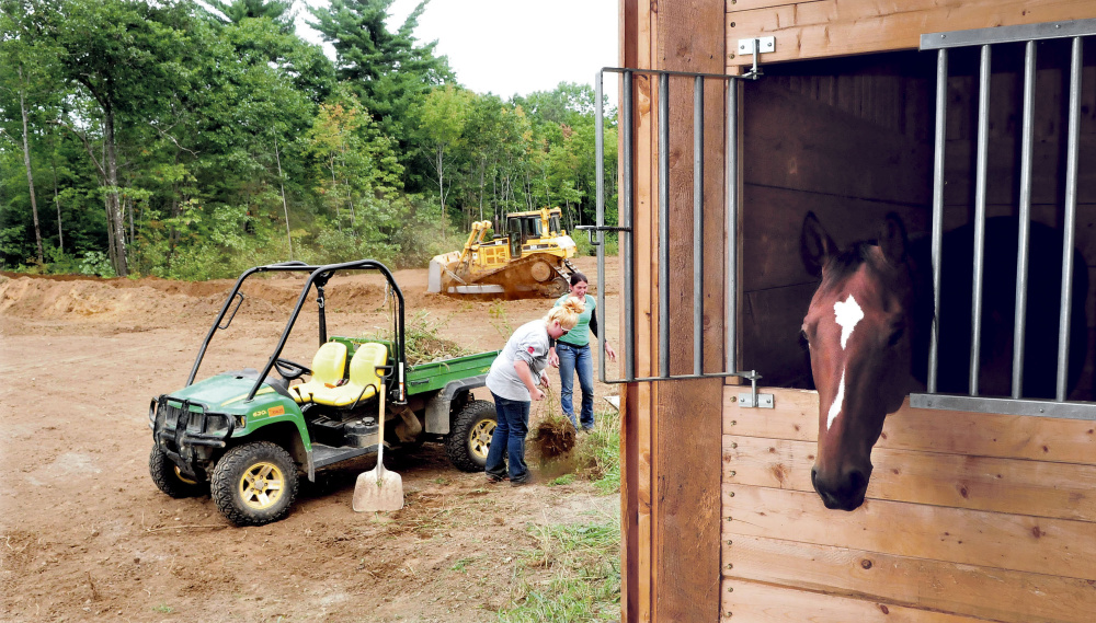 Stephanie Wrigley, left, and Milynn Phair, members of Halee Cummings' family, pick up loose material Tuesday as a bucket loader operator creates a family cemetery at the Paquette farm in Sidney. Cummings died Friday in an all-terrain vehicle accident nearby. One of her horses looks out of his stall.