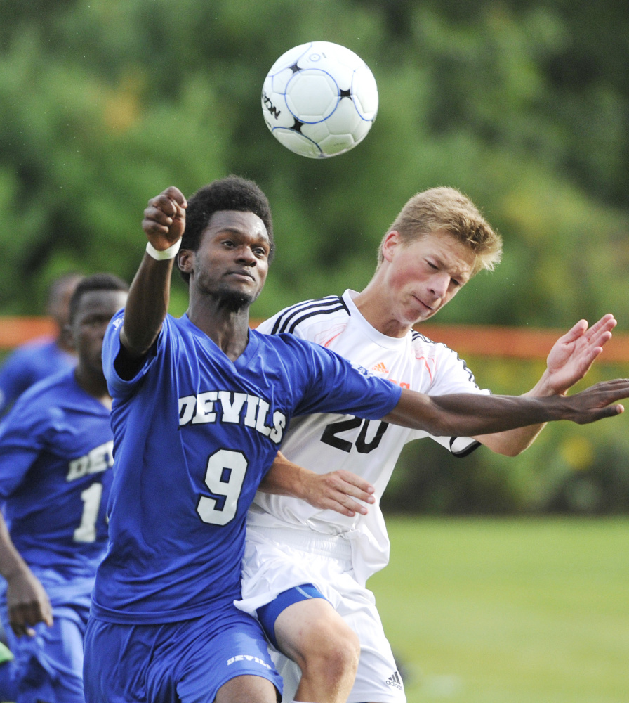 Maslah Hassan of Lewiston heads a shot on goal Tuesday while defended by Max Gramins of Brunswick during undefeated Lewiston's 5-0 victory.
