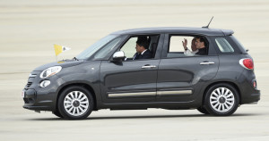 Pope Francis waves from inside a Fiat 500 as he leaves Andrews Air Force Base in Md., on Tuesday.