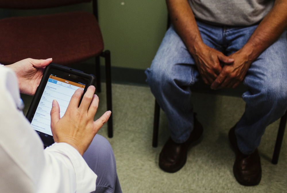 """Physician assistant Molly Boyd uses the Health eVillage tablet while assisting a patient at the Harrington Family Health Center in Harrington, a small coastal community in Washington County. The tablet is loaded with medical apps that provide """"an electronic library at your fingertips,"""" said Lee Umphrey, CEO of the health center."""