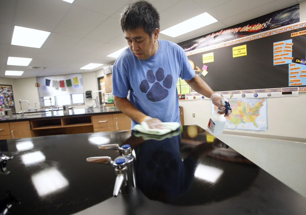 Lodel Seneres, a custodian at Saco Middle School, wipes down countertops in a science classroom.