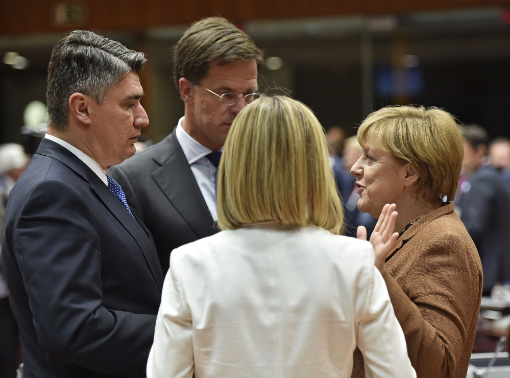 Croatian Prime Minister Zoran Milanovic  and Dutch Prime Minister Mark Rutte listen to German Chancellor Angela Merkel, from left,  as they arrive for an emergency EU heads of state summit on the migrant crisis at the EU Commission headquarters in Brussels on Wednesday, Sept. 23, 2015.  (AP Photo/Martin Meissner)