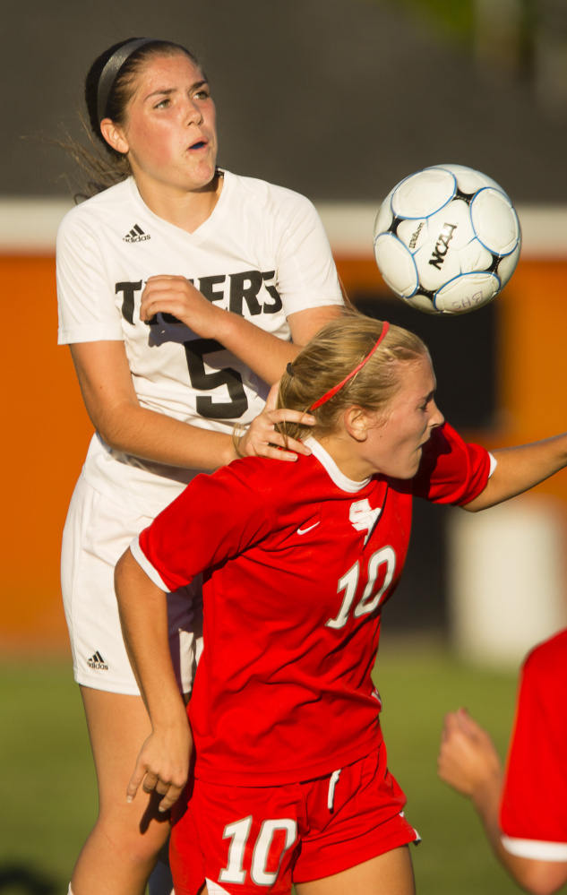 Madison Cantara of Biddeford goes over Callie O'Brien of South Portland to head the ball away Wednesday during South Portland's 2-1 victory in an SMAA game at Biddeford. O'Brien scored a goal.