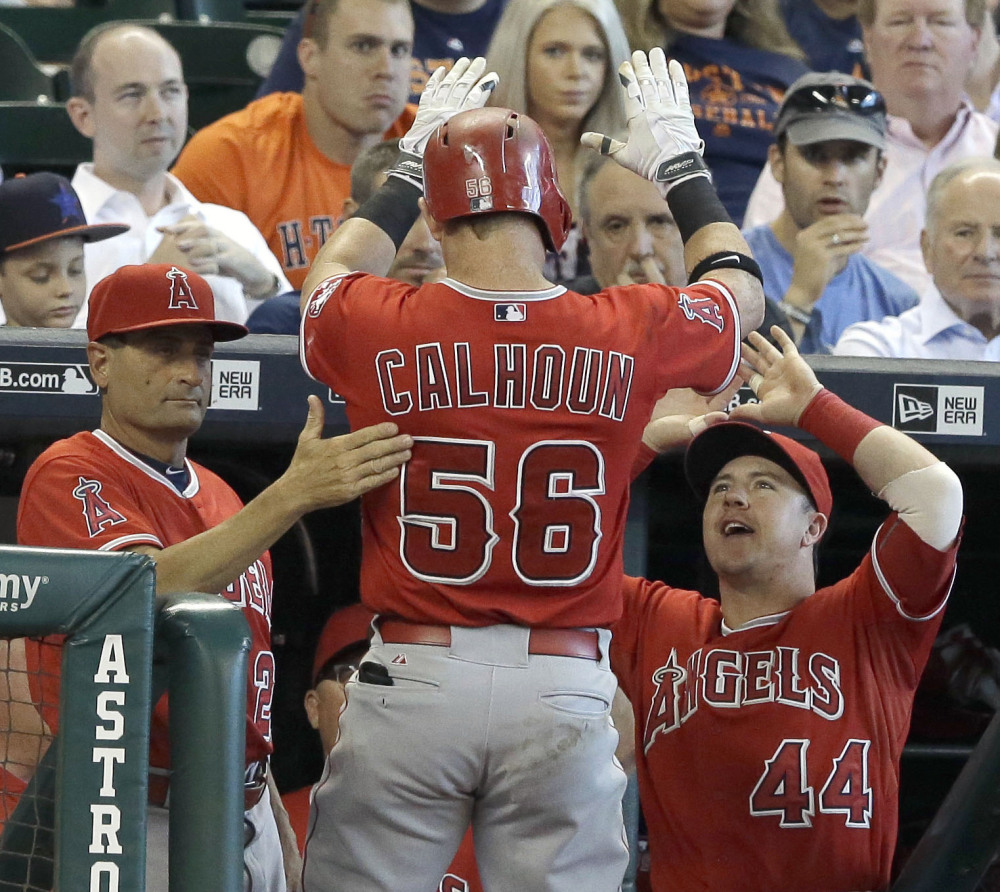 Kole Calhoun of the Angels is welcomed back to the dugout after hitting a solo homer in a 6-5 Los Angeles win over the Astros at Houston on Wednesday.