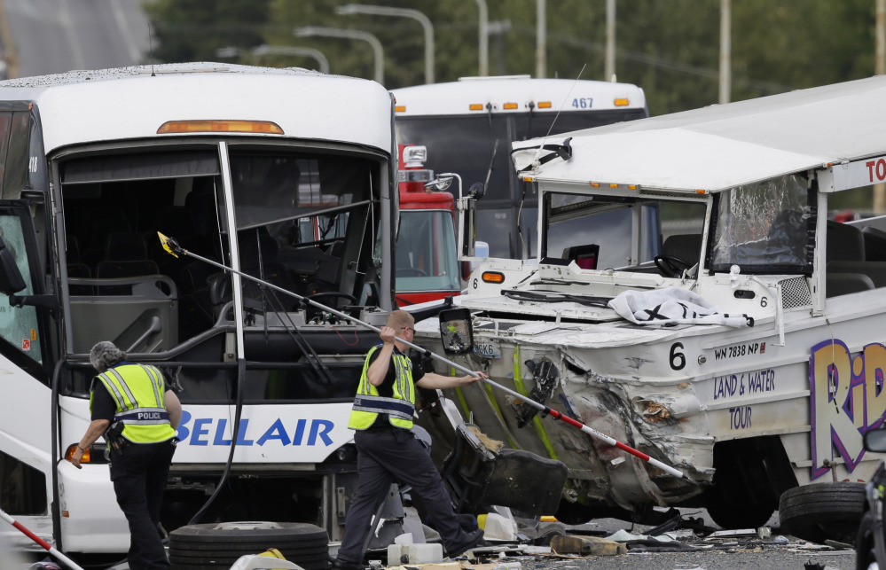 "Officials work at the scene of a crash involving a ""Ride the Ducks"" amphibious vehicle and a charter bus. Dozens  were seriously injured in the collision Thursday."