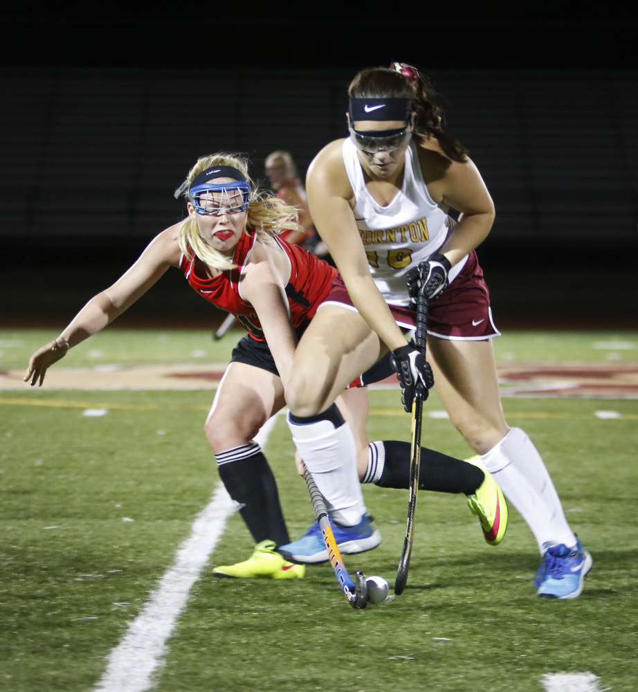 Scarborough's Lucy Malia, left, puts defensive pressure on Thornton Academy's Emma Dutremble in the second half of their field hockey game Thursday night at Saco. Scarborough won 2-1 to improve to 7-1.